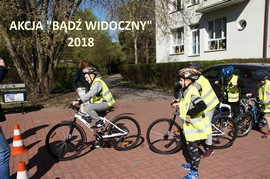 wychowankowie w kaskach i kamizelkach odblaskowych na rowerach